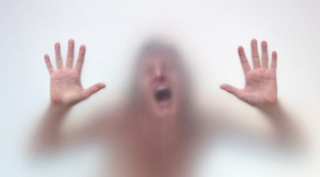 Naked captive woman in anguish --- Image by © Miguel Sobreira/ /age fotostock Spain S.L./Corbis